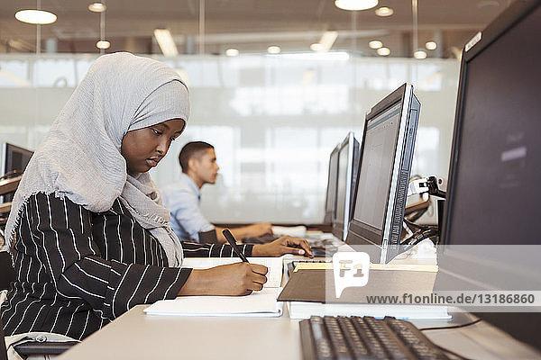 Seriöse Studentin schreibt in Buch  während sie den Computer in der Universitätsbibliothek benutzt