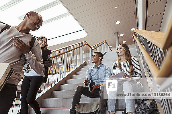 Happy multi-ethnic friends talking while sitting on staircase in university