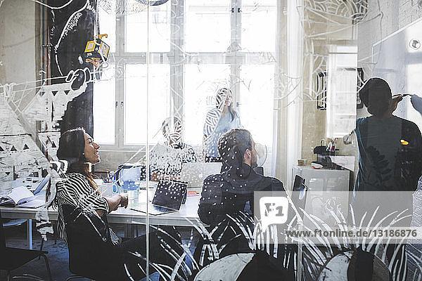 Kreative Geschäftsleute betrachten eine Kollegin  die bei einer Besprechung im Büro am Whiteboard ihre Strategie erklärt