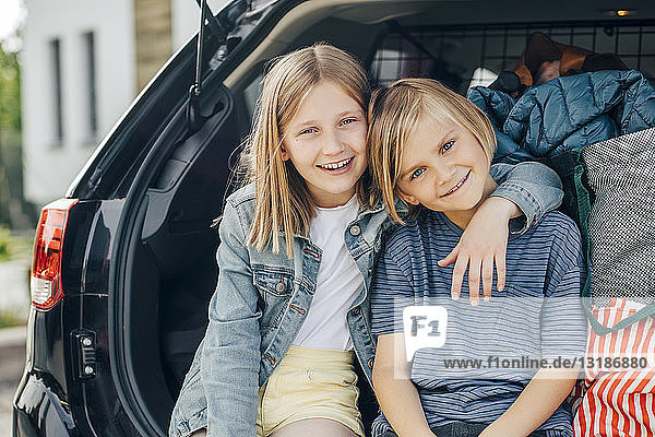 Portrait of smiling blond girl sitting with arm around sister in car trunk against house