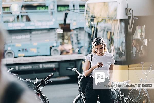 Junge Frau benutzt Mobiltelefon  während sie auf der Straße in der Stadt an den Fahrrädern steht