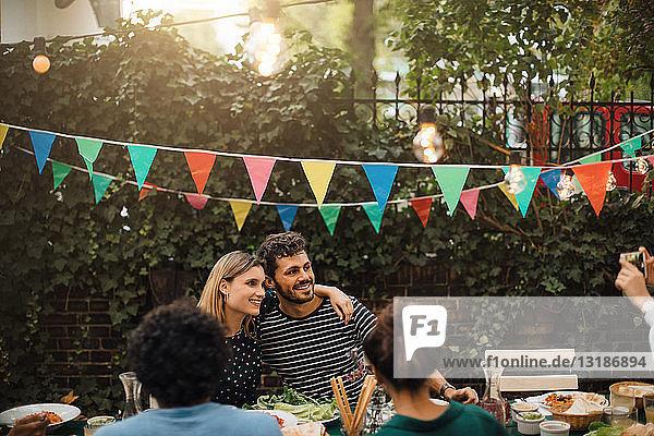 Lächelnde Freunde und Freundinnen posieren während einer Dinnerparty im Hinterhof für ein Foto