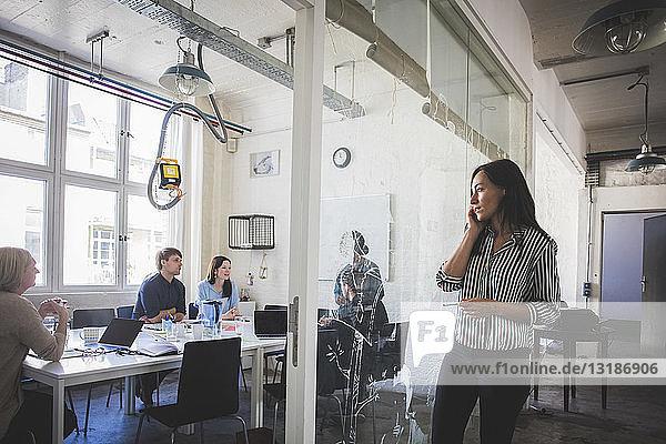 Geschäftsfrau sieht Kollegen bei der Strategieplanung im Sitzungssaal an  während sie mit dem Handy telefoniert