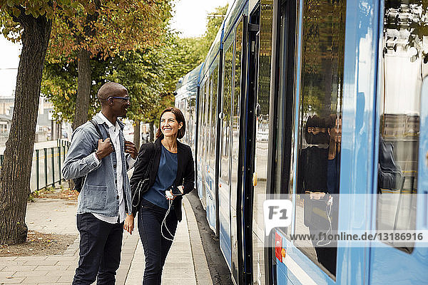 Smiling multi-ethnic commuters standing by blue tram in city