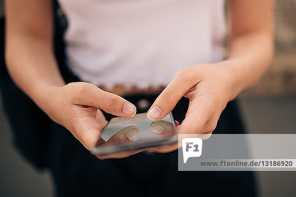 Mittendrin junge Frau beim SMS-Versand über Mobiltelefone in der Stadt