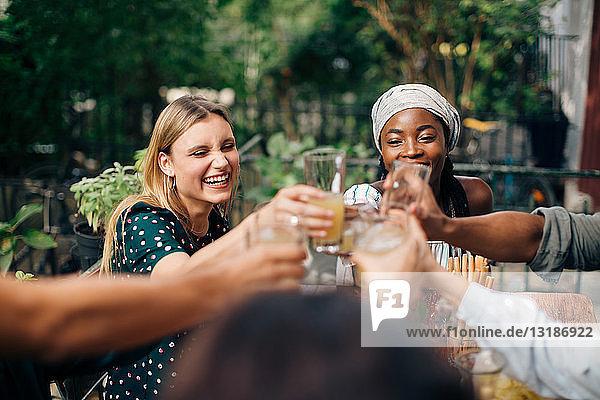 Multiethnische Freunde stoßen auf Getränke an  während sie auf dem Balkon sitzen