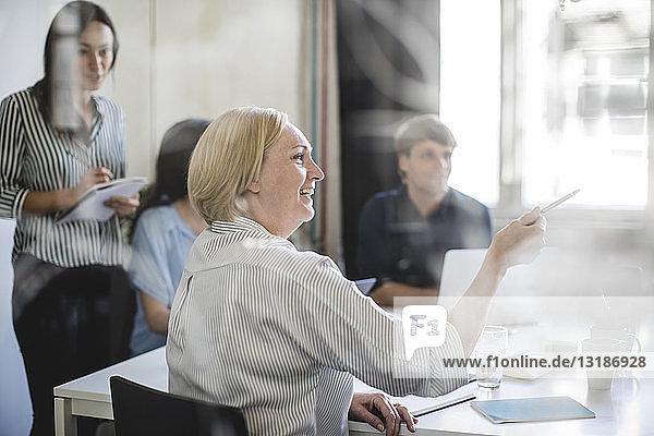 Lächelnde Geschäftsfrau zeigt während einer Sitzung mit Kollegen im Sitzungssaal