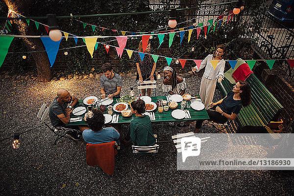 Schrägansicht auf multiethnische Freunde  die während einer Gartenparty am Tisch zu Abend essen