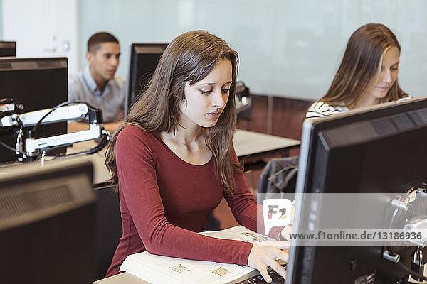 Junge Schülerin benutzt Computer  während sie mit Freunden in der Bibliothek der High School sitzt