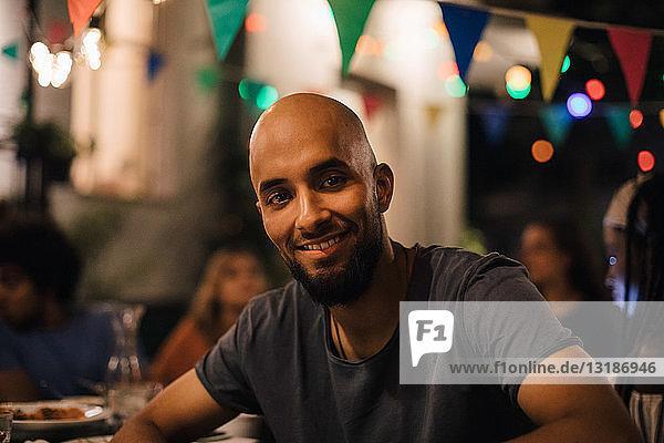 Porträt eines lächelnden jungen Mannes mit rasiertem Kopf  der während einer Dinnerparty im Hinterhof sitzt