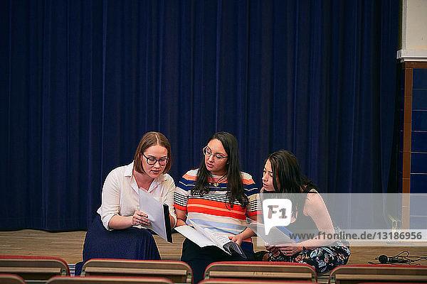 Multi-ethnische Frauen diskutieren über Notenblätter im Auditorium