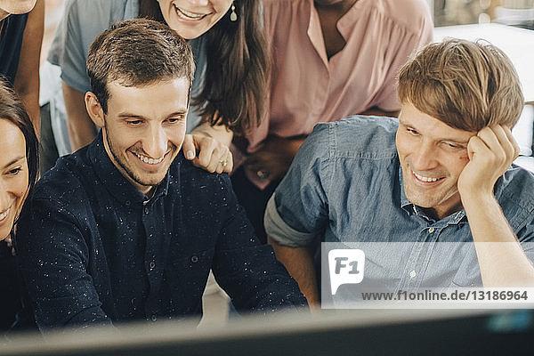 Lächelnde kreative Geschäftsleute  die während einer Besprechung im Büro auf den Computermonitor schauen