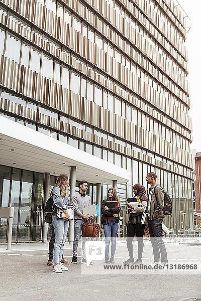 Multi-ethnische Studenten im Gespräch  während sie sich gegen Gebäude auf dem Universitätsgelände stellen