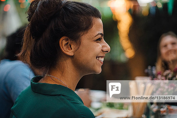 Smiling young woman looking away during dinner party in backyard