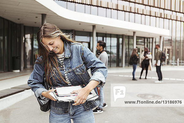 Lächelnde junge Frau hält Bücher  während sie auf dem Universitätscampus steht