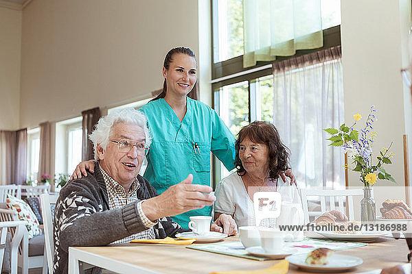Lächelnde Gesundheitshelferin und ältere Frau  die dem Mann beim Frühstück zu Hause zuhört