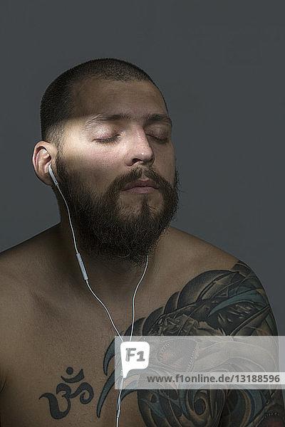 Gelassener Mann mit nacktem Oberkörper  Bart und Tattoos  der mit Ohrhörern Musik hört