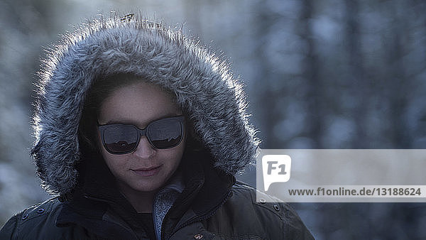 Portrait woman in winter fur hood and sunglasses