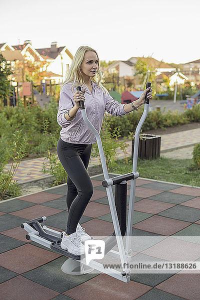 Fit woman using elliptical machine on patio