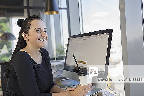 Smiling woman drinking coffee and using computer at internet cafe