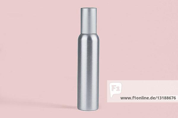 Metal bottle against pink background
