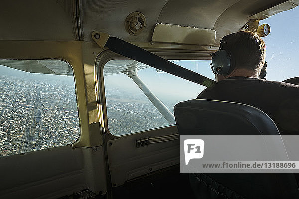 Man flying small airplane over city