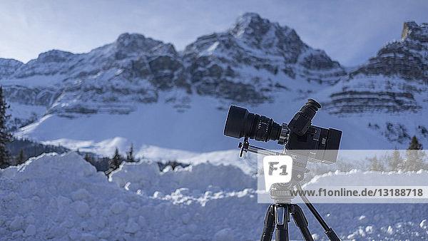 Video camera on tripod below snowy mountain landscape  Banff  Alberta  Canada Video camera on tripod below snowy mountain landscape, Banff, Alberta, Canada