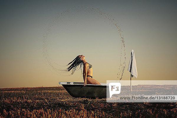 Woman in bikini splashing hair in bathtub in rural field
