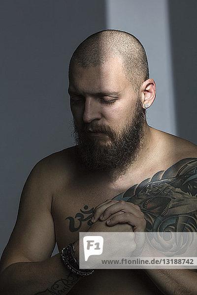 Mann mit nacktem Oberkörper und Tattoos