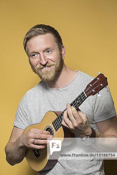 Portrait lächelnder Mann spielt Ukulele
