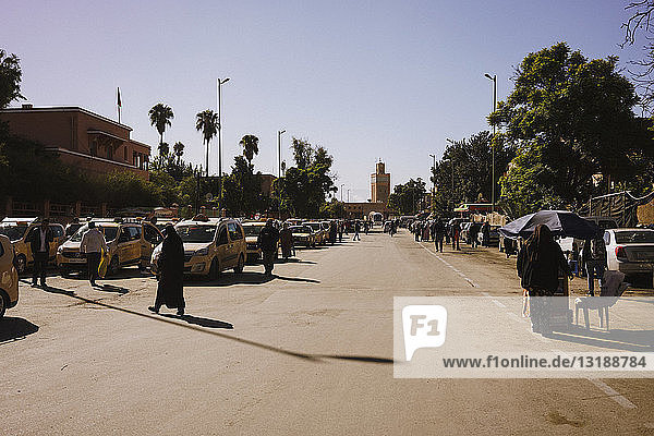 Cars and pedestrians on sunny road  Marrakesh  Morocco