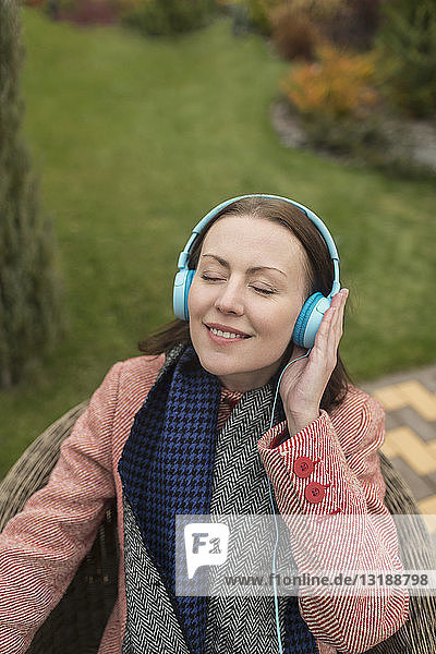 Serene woman listening to music with headphones outside