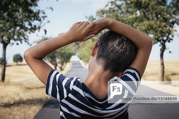 Boy standing on rural road