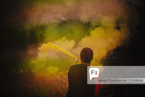 Male DJ on stage holding smoke bomb