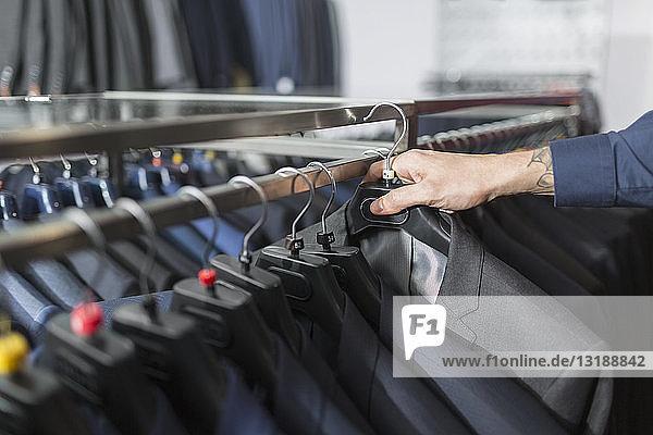 Mann greift in einem Herrenbekleidungsgeschäft nach einem Anzug auf einem Bügel