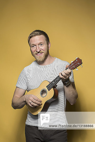 Portrait smiling man playing ukulele