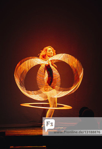 Woman performing on stage  spinning illuminated rings