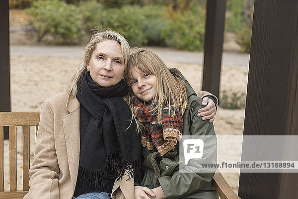 Portrait affectionate mother and daughter hugging on park bench