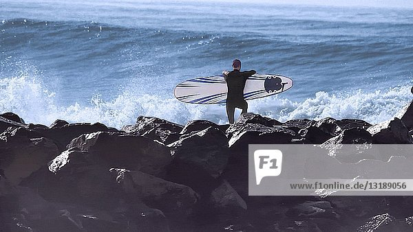 Rear View of Surfer with Surfboard Watching Crashing Waves
