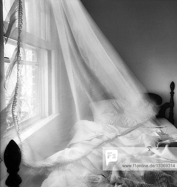 Vorhang weht über Bett
