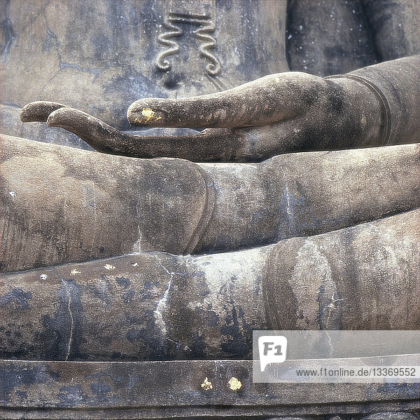Hand on crossed legs of Buddha statue