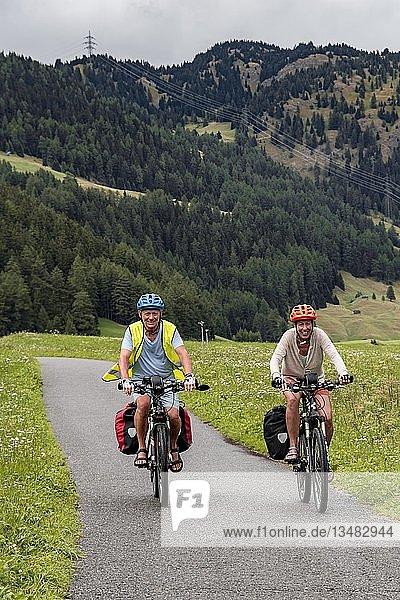 Fahrradfahrer mit Mountainbikes und Sicherheitsweste  auf dem Radweg Via Claudia Augusta  Alpenüberquerung  hinten Sonnenspitze  Berglandschaft  bei Ehrwald  Tiroler Alpen  Tirol  Österreich  Europa