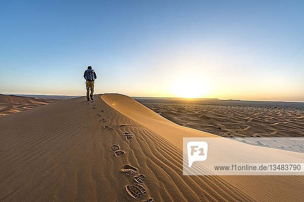 Junger Mann auf einer Sanddüne bei Sonnenaufgang  Erg Chebbi  Merzouga  Sahara  Marokko  Afrika