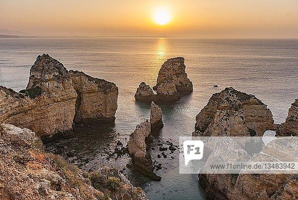 Sonnenaufgang über dem Meer  Felsenküste aus Sandstein  Felsformationen im Meer  Algarve  Lagos  Portugal  Europa
