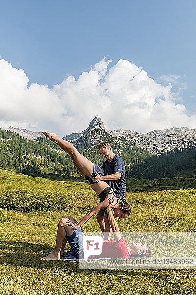 Junge Frau und junger Mann machen Acro-Yoga  Berglandschaft  Nationalpark Berchtesgaden  Berchtesgadener Land  Oberbayern  Bayern  Deutschland  Europa