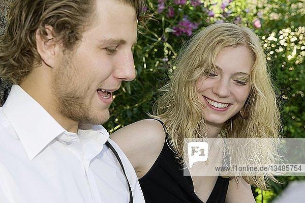 Ein junges Paar sitzt im Garten und führt eine angeregte Unterhaltung  Deutschland  Europa