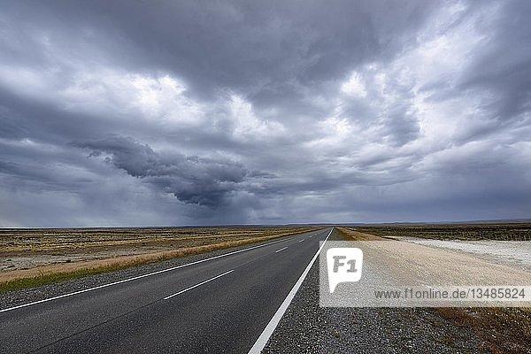 Straße mit Gewitterstimmung durch die Pampa von Patagonien  bei Rio Gallegos  Argentinien  Südamerika