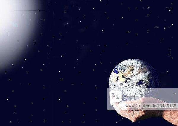 In einer ausgestreckten Hand die ins Weltall ragt liegt beschützt unsere Erde