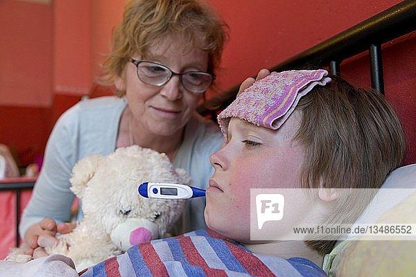 Mutter tröstet kranken Sohn im Bett,  Symbolbild,  Erkältung,  Pflege,  Kindheit,  Eltern,  Deutschland,  Europa