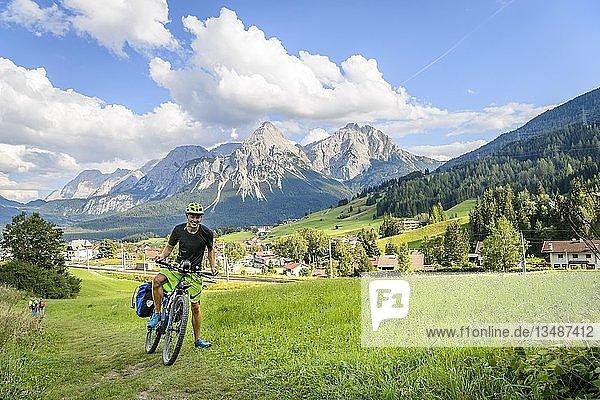 Fahrradfahrer auf Radtour mit Mountainbike  auf dem Radweg Via Claudia Augusta  hinten Ehrwalder Sonnenspitze  Alpenüberquerung  Berglandschaft  Alpen  Ehrwalder Becken  bei Ehrwald  Tirol  Österreich  Europa